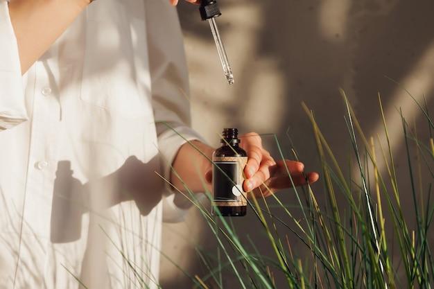 Mani della donna che tengono le bottiglie di olio dei cosmetici o di massaggio. chiudere l'olio essenziale sulla sedia. vista ad alto angolo della bottiglia di olio da massaggio su sfondo foglia. concetto di stile di vita sano e cura di sé. copia spazio