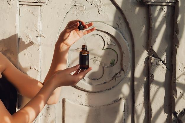 Mani della donna che tengono le bottiglie di olio dei cosmetici o di massaggio. chiudere l'olio essenziale sulla sedia. vista ad alto angolo della bottiglia di olio da massaggio su sfondo vecchio. concetto di stile di vita sano e cura di sé. copia spazio