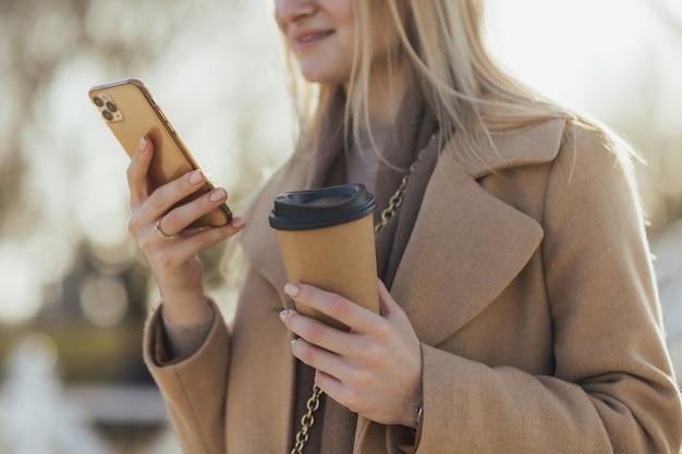 Mani della donna che tengono la tazza di carta di caffè e smartphone nel parco