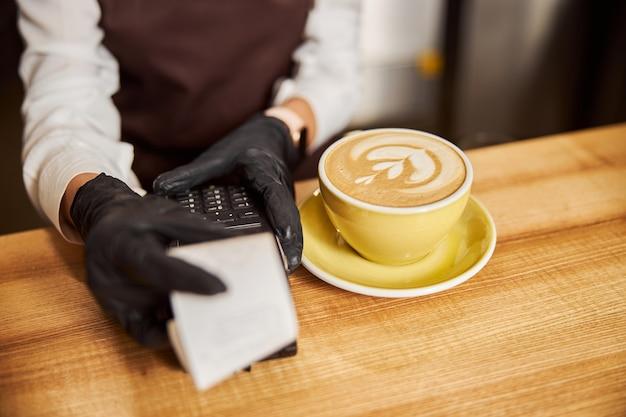 Mani di donna che tengono la ricevuta di pagamento sul tavolo