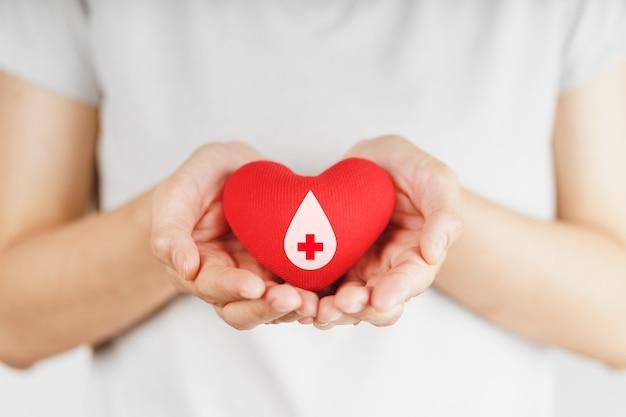 Mani della donna che tengono cuore rosso con il segno del donatore di sangue concetto di assistenza sanitaria, medicina e donazione di sangue