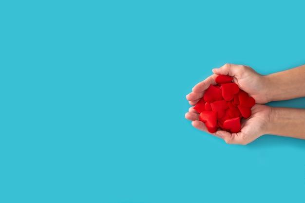 Mani della donna che tengono i cuori rossi su priorità bassa blu