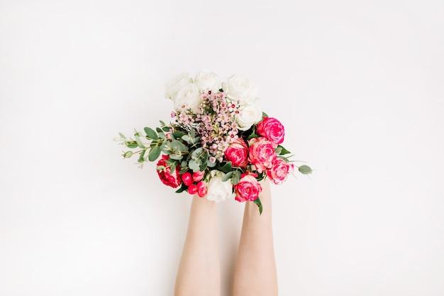 Mani di donna che tengono bouquet di fiori da sposa con rose, ramo di eucalipto, fiori di campo. disposizione piatta, vista dall'alto