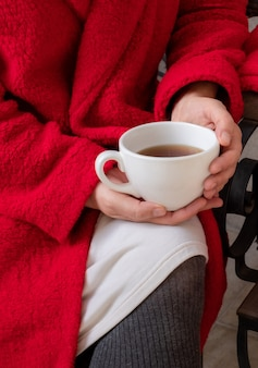 Mani della donna che tengono tazza bianca di tè o caffè