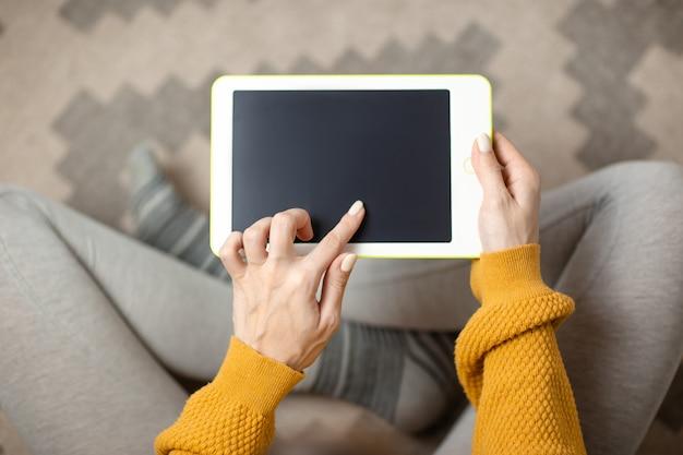 La donna passa la tenuta della compressa bianca. ministero degli interni mentre auto-isolamento, lavoro da casa. formazione online, e-learning durante la quarantena.