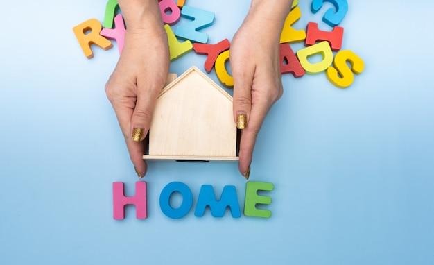 Mani di donna che tengono casa in legno.