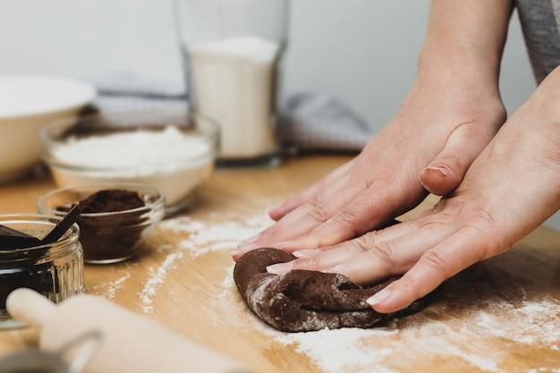 Mani della donna che impastano la pasta del cioccolato, cucinando i biscotti o dessert. cucinare a casa.