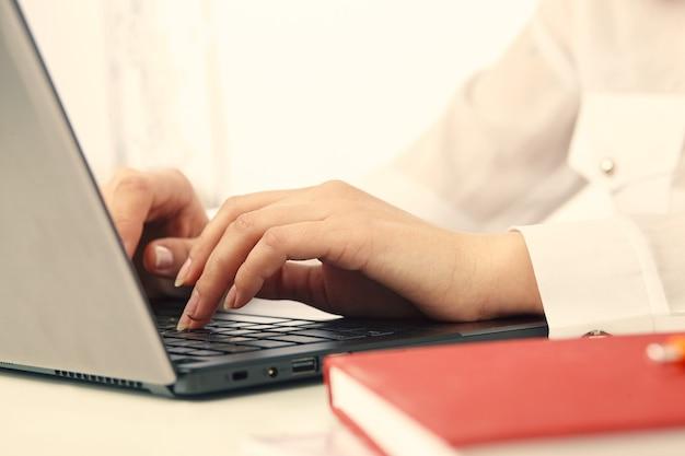Mani e laptop della donna