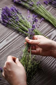 Mani di donna che fanno un bouquet di fiori di lavanda naturale