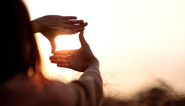 Mani di donna che fanno gesto di cornice con il tramonto