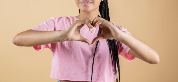 Mani della donna che fanno gesto del cuore