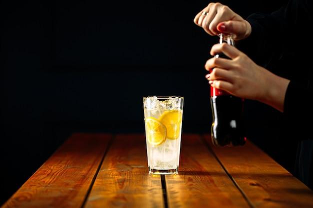 Mani della donna che fanno cocktail di tè freddo di long island
