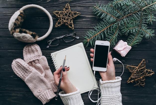 La donna passa in guanti e taccuino con la lista di obiettivi sulla tavola d'annata del turchese da sopra, concetto di pianificazione di natale. decorazioni natalizie con notebook e smartphone.