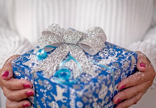 Mani di donna che offrono un regalo di natale in una carta blu con un grande fiocco d'argento