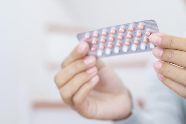 Mani della donna che aprono le pillole anticoncezionali in mano. mangiare pillola contraccettiva.