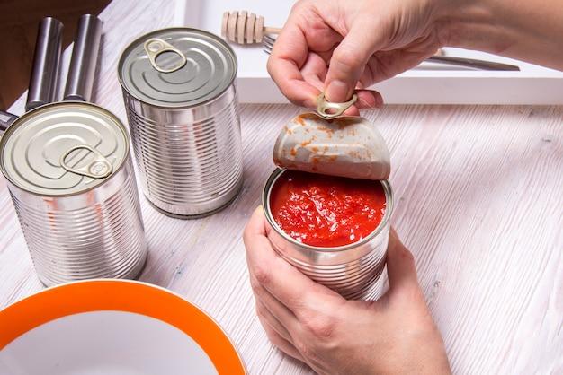 La donna passa l'apertura del barattolo di latta con i pomodori inscatolati, tavolo da cucina