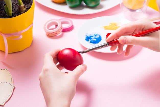 Mani di donna che dipingono le uova di estere sulla scrivania rosa