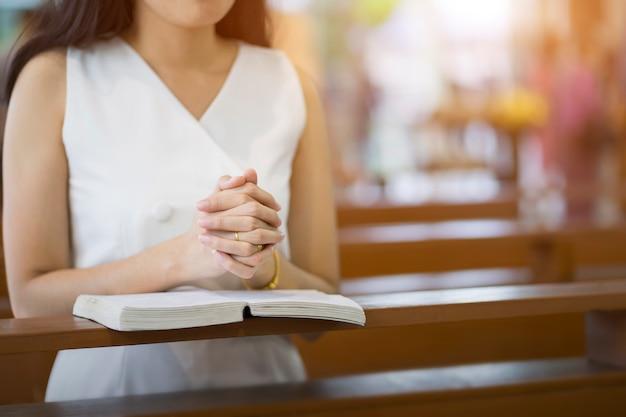 Mani della donna che pregano su una bibbia santa in chiesa per il concetto di fede, spiritualità e religione cristiana.
