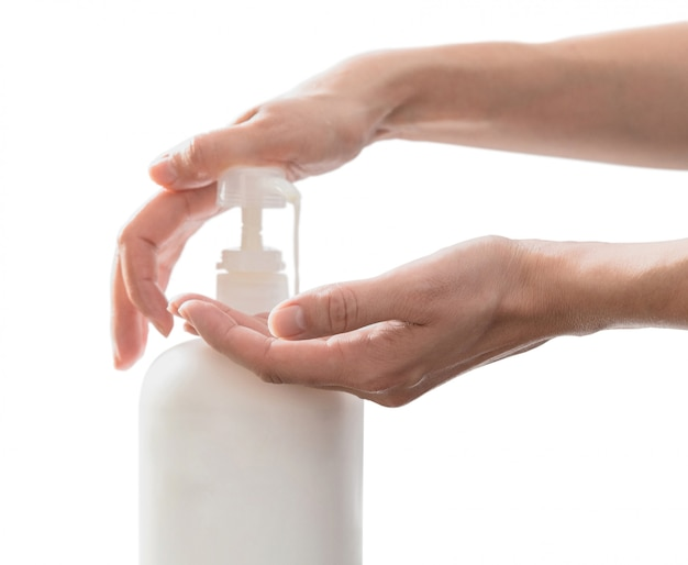 Mani della donna che spingono la bottiglia di plastica del sapone della pompa, isolata su bianco con lo spazio della copia