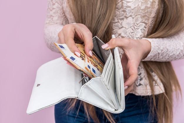 Le mani della donna mettono le banconote in euro nella borsa