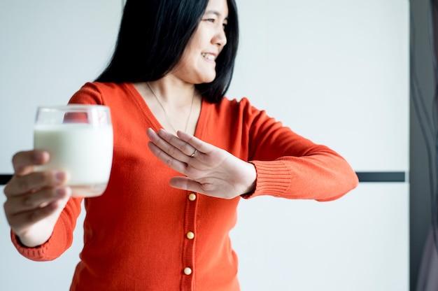 Mani di donna che rifiutano un bicchiere di latte, femmina con latte allergico, concetto di intolleranza al lattosio