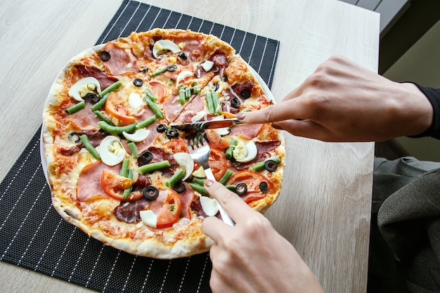 Mani della donna affettare pizza fresca con fagioli, formaggio, prosciutto, uova, peperoni e verdure