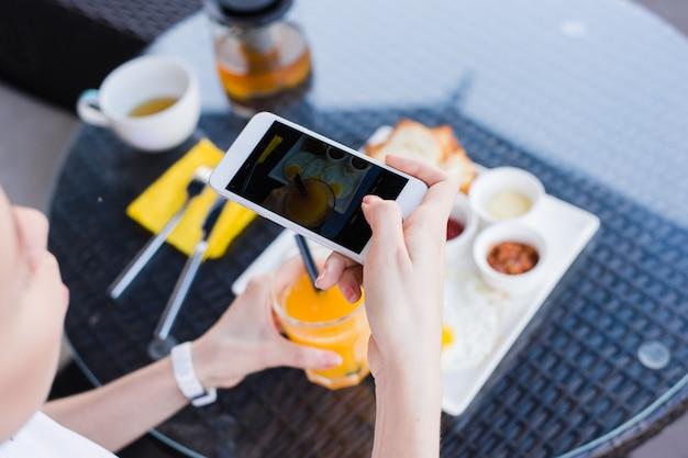 La donna passa la presa della foto dell'alimento dal telefono cellulare. fotografia di cibo. deliziosa colazione