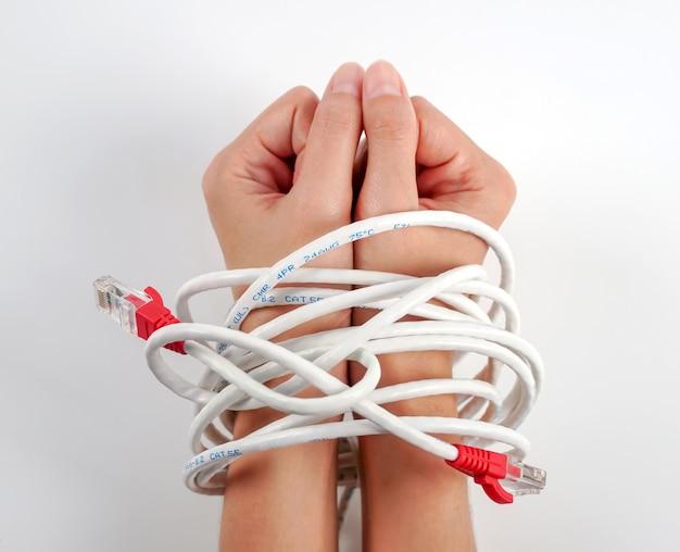 Mani di donna legate con cavo di rete