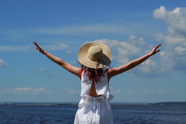 Donna con le mani in alto sulla riva del fiume, vista posteriore