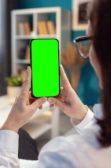 La donna passa verticalmente tenendo il cellulare con schermo verde, atmosfera familiare