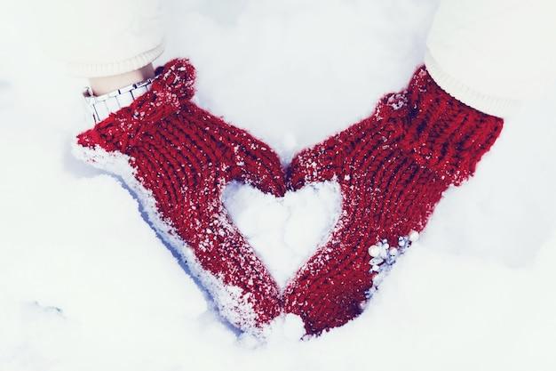 Mani della donna in guanti invernali. concetto di stile di vita e sentimenti a forma di simbolo del cuore