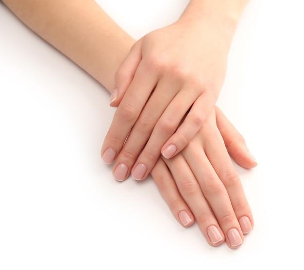 Mani della donna con bella manicure su bianco