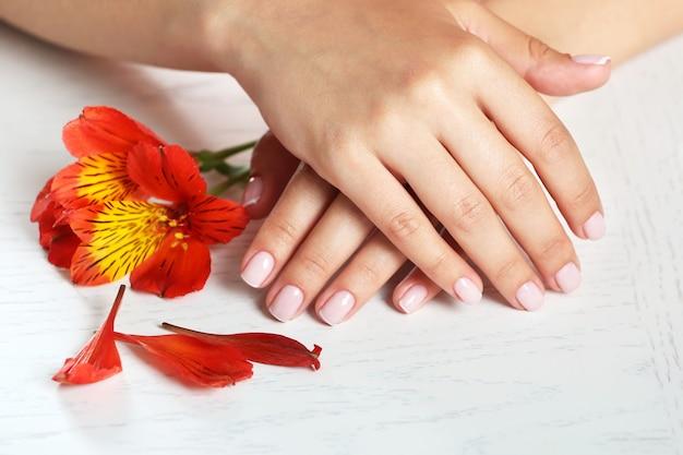 Mani della donna con french manicure e fiori sul tavolo