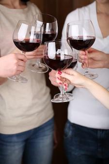 Mani di donna con bicchieri di vino in primo piano