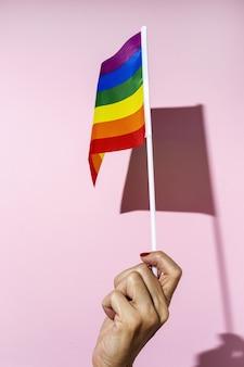 Mani di donna con bandiera lgbt su sfondo rosa