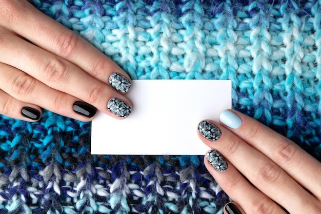 Mani della donna con il biglietto da visita della tenuta del manicure