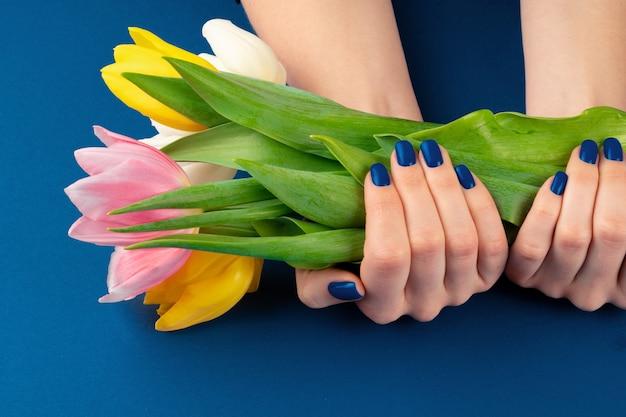 Mani della donna con il manicure che tiene tulipani colorati su sfondo blu
