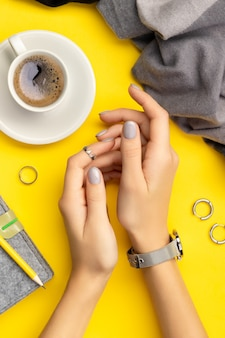 Mani della donna con manicure minima su giallo