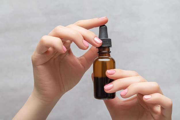 Mani di donna con manicure rosa. bottiglia di olio essenziale della tenuta femminile. concetto di benessere sanitario femminile.