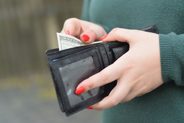 Le mani della donna con le unghie rosse tiene la borsa degli uomini di colore con molte banconote da cento dollari