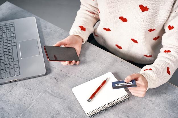 Mani di donna con telefono rosso e carta di credito shopping online