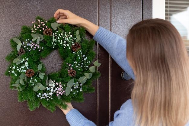 Donna che appende ghirlanda di natale sulla porta d'ingresso che decora la casa per le vacanze di natale