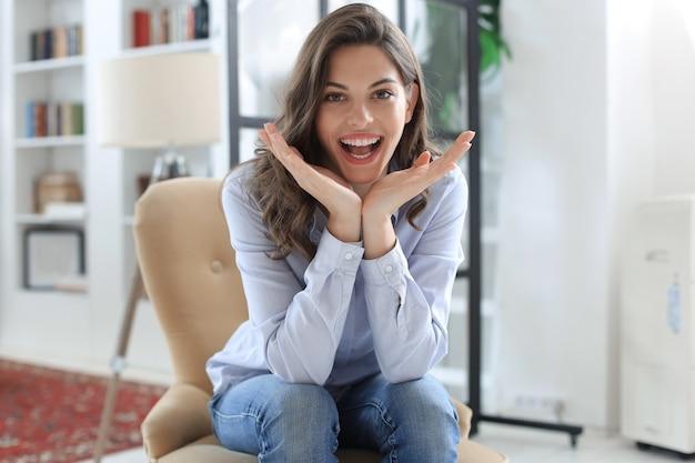 Donna felice sulla poltrona sorridente e allungando guardando la fotocamera.
