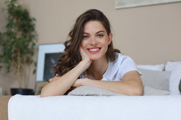 Donna felice sul letto sorridente e allungando guardando la fotocamera.
