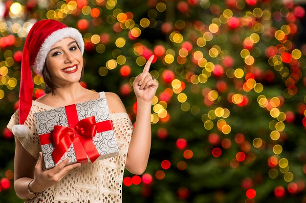 Donna felice sorriso punto dito che mostra lo spazio vuoto copia lato, giovane donna eccitata indossare cappello santa, prodotto pubblicitario su bokeh luci di natale