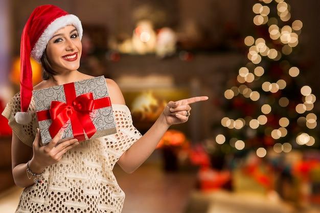 Donna felice sorriso punto dito mostrando lato spazio vuoto copia, giovane donna eccitata indossare cappello santa, prodotto pubblicitario isolato su bokeh luci di natale