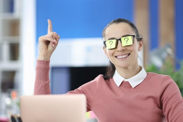 La donna ha un adesivo colorato con un punto interrogativo sugli occhiali e alza i pollici. cerca nuove idee e soluzioni nel concetto di business