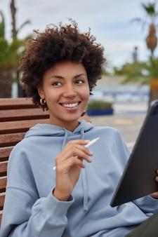 La donna ha lavori a distanza crea contenuti grafici la pubblicazione usa lo stilo elettronico indossa una felpa con cappuccio posa all'esterno gode del suo hobby preferito naviga sui social media tramite l'applicazione
