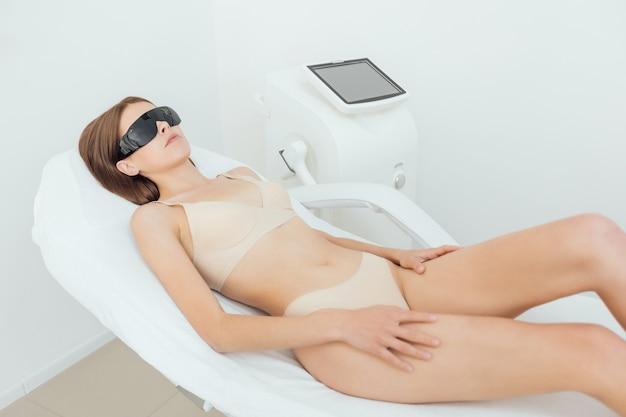 La donna ha una procedura di epilazione laser e cosmetologia