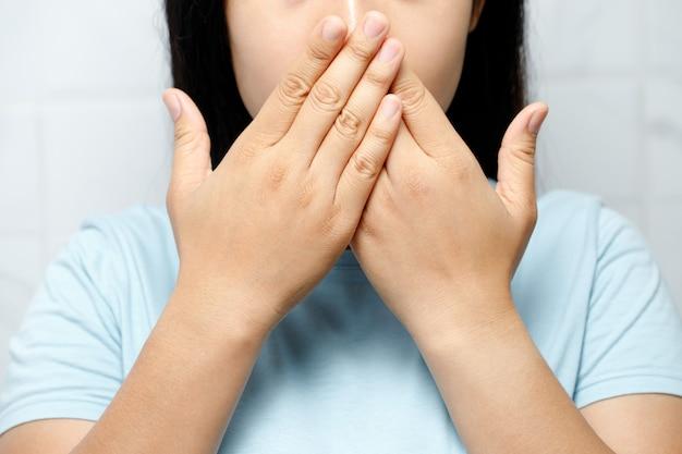 La donna ha problemi orali, ha l'alitosi
